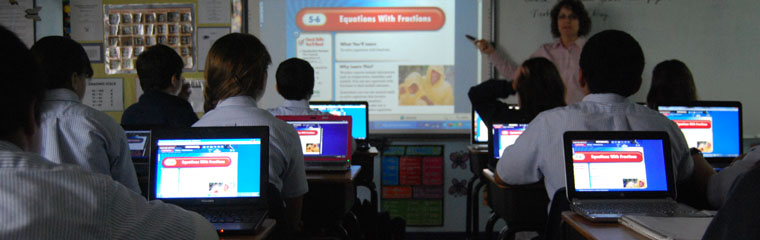 Students in a classroom on laptops facing a teacher presenting with a projector