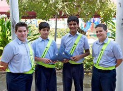 Four boys, two of them holding a folded American Flag smiling